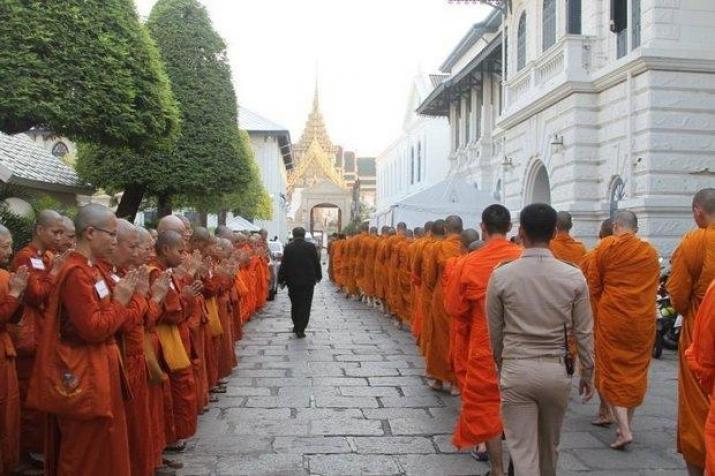 Après s'être vu refusé l'accès à la cérémonie funéraire du roi Bhumibol Adulyadej, les bikkhunis, à gauche, saluent respectueusement les moines escortés dans le Grand Palais pour assister à la cérémonie. (de Bangkokpost.com)